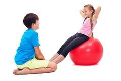 Kinder, die zusammen - unter Verwendung eines großen gymnastischen Gummiballs trainieren Lizenzfreies Stockfoto