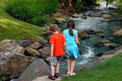 Kinder durch Stream lizenzfreie stockbilder