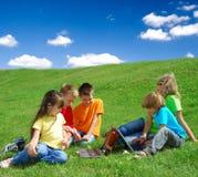 Kinder in einer Wiese mit Laptopen Stockbild