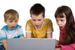 Kinder entsetzt durch etwas auf Computer lizenzfreies stockbild