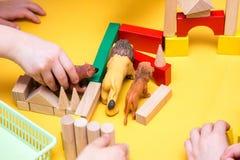Kinder errichten einen Zoo von hölzernen Ziegelsteinen auf Tabelle Stockfotografie