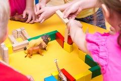 Kinder errichten einen Zoo von hölzernen Ziegelsteinen auf Tabelle Lizenzfreies Stockbild