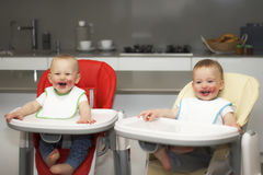 Kinder essen Blaubeeren in einem hohen Babystuhl Die Jungen haben ein schmutziges Gesicht stockfotos