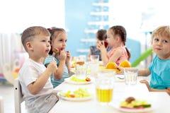 Kinder essen in der Kindertagesst?ttenmitte zu Mittag Kinder, die gesunde Nahrung im Kindergarten essen stockfotografie