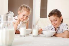 Kinder essen Getreide mit Milch lizenzfreies stockbild