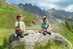 Kinder essen Käse und Brot auf großem Stein in den Bergen Stockfotografie
