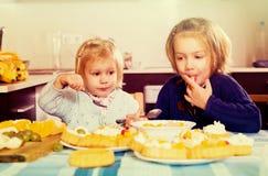 Kinder essen Kuchen an der Küche stockfotos