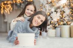 Kinder, Familie und Feierkonzept Entzückende Frau in gestrickter Strickjacke hält weißen Präsentkarton und kleines Kind steht hin lizenzfreies stockbild