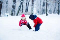Kinder formen den Schneemann Stockfotografie