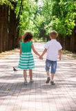 Kinder gehen auf die Allee im Park lizenzfreie stockbilder