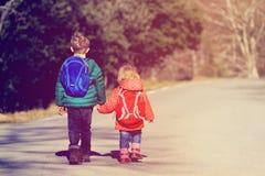 Kinder gehen zur Schule - der Bruder und Schwester mit Rucksäcken gehend auf die Straße Lizenzfreie Stockbilder