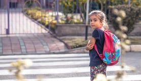 Kinder gehen zur Schule, ein glücklicher Student mit einem Rucksack, Kreuze stockfoto