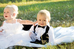 Kinder gekleidet als Braut und Bräutigam Stockfotos