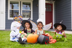Kinder gekleidet in den Trick-oder Behandlungs-Kostümen auf Rasen stockbild