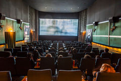 Kinder genießen einen Film an einem alten traditionellen Kino lizenzfreie stockfotos