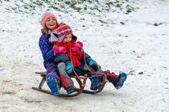 Kinder genießen, im Schneepark snowshoeing, wohin das Gras herauskommt stockbild