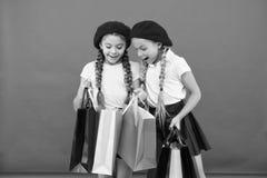 Kinder genie?en kaufenden roten Hintergrund Besuchs-Kleidungsmall Rabatt- und Verkaufskonzept Kindernette M?dchen das Einkaufen h lizenzfreie stockfotografie