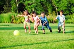Kinder gruppieren das Spielen mit Kugel Lizenzfreie Stockfotos