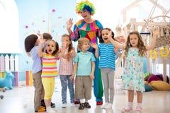 Kinder gruppieren mit dem Clown, der Geburtstagsfeier feiert lizenzfreie stockfotografie