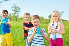 Kinder gruppieren mit Spielzeugwassergewehren Stockfotos
