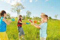 Kinder gruppieren mit Wassergewehren und Einweichern Stockfoto