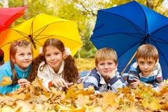 Kinder gruppieren unter Regenschirmen Stockfoto