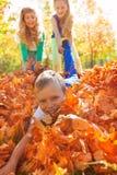 Kinder haben den schleppenden Jungen des Spaßes, der auf dem Boden legt Stockbild