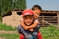 Kinder haben den Spaß, der im zentralen asiatischen Dorf im Freien ist Stockfotografie