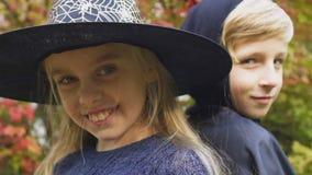 Kinder in Halloween-Kostümen, die für Kamera, Vorbereitung für furchtsame Partei aufwerfen stock video