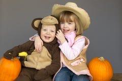 Kinder in Halloween-Kostümen, die mit Kürbisen sitzen Stockfoto