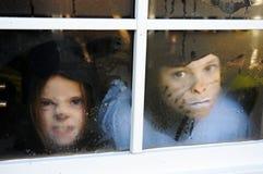 Kinder hinter einem Fenster mit Regentropfen lizenzfreie stockfotografie