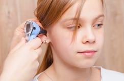 Kinder-HNOkontrolle - Untersuchungsohr des Kinderarztes vom grundlegenden Altersmädchen mit Otoscope in der pädiatrischen Klinik stockfotografie