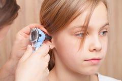 Kinder-HNOkontrolle - Untersuchungsohr Doktors vom grundlegenden Altersmädchen mit Otoscope lizenzfreie stockbilder