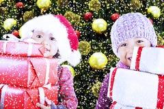 Kinder holen Weihnachtsgeschenke unter Baum Stockbilder