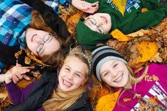 Kinder im Freien auf Herbstblättern Stockbilder