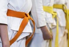 Kinder im Kimono, der in einer Linie auf Kampfkunstklasse sitanding ist Lizenzfreies Stockfoto