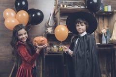 Kinder im Kostüm von Monstern für Halloween stehen nahe bei den Regalen und halten einen Kürbis und Ballone Stockbilder