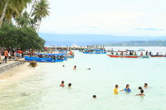 Kinder im Meer und Pilger, die zu Mansinam kommen Lizenzfreie Stockfotos