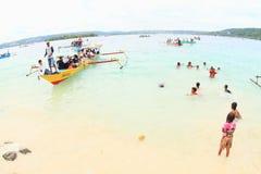 Kinder im Meer und Pilger, die zu Mansinam kommen Stockfotografie