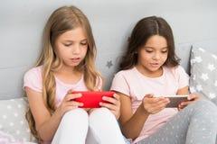 Kinder im Pyjama wirken auf Smartphones ein Anwendung für Kinderspaß Elterliches Beratungs Internet-Surfens und -abwesenheit stockfotografie
