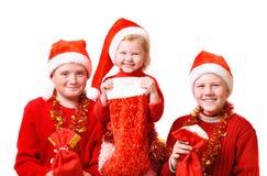 Kinder im roten Weihnachtshut Stockbild