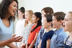 Kinder im Schulchor, der vom Lehrer angeregt wird Lizenzfreie Stockfotos
