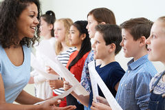 Kinder im Schulchor, der vom Lehrer angeregt wird Stockbild
