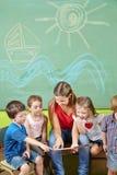 Kinder im Vorschullesebuch Stockfotos