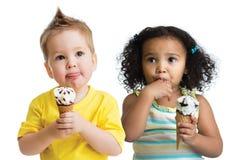 Kinder Junge und Mädchen, welche die Eiscreme lokalisiert isst Stockbilder