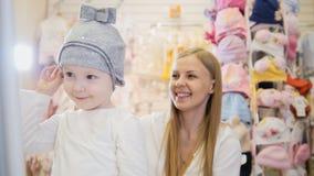 Kinder kleiden Speicher - kleines blondes Baby mit der Mutter, die Einkaufs- und Kaufenhut tut Lizenzfreie Stockfotos