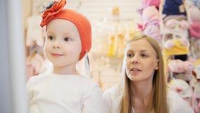Kinder kleiden Speicher - kleines blondes Baby mit der Mutter, die Einkaufs- und Kaufenrothut tut Stockbild