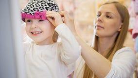 Kinder kleiden Speicher - kleines blondes Baby mit der Mutter, die Einkaufs- und Kaufenrothut tut Stockfotos