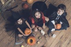 Kinder kleideten in den Kostümen sitzen auf dem Boden und schauen oben an Vor ihnen die Landschaft für Halloween Stockfotografie