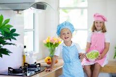 Kinder kochen in der wei?en K?che kleines Baby mit einem gro?en L?ffel lizenzfreie stockbilder